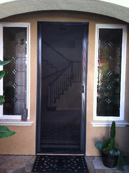 tall_bronze_roll_away_disappearing_screen_door_in_use